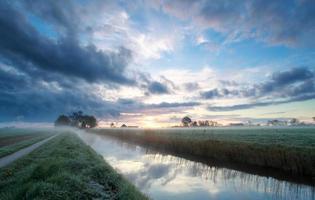soluppgång på holländsk jordbruksmark på sommaren