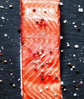 filé av salt lax med kryddig peppar och havssalt foto