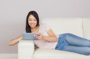 ganska asiatisk tjej som ligger på soffan med den digitala minnestavlan foto