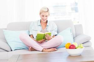 ganska blond kvinna som läser en bok i soffan foto