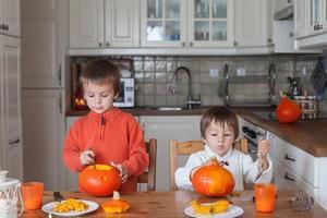två bedårande pojkar som förbereder jack o-lykta för halloween foto