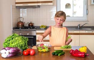 ung flicka matlagning. hälsosam mat - grönsaksallad. foto