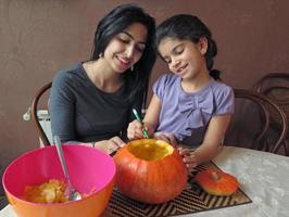 mor och dotter som har kul medan de snider en halloween pumpa foto