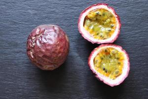 två passionsfrukter, en hel, den andra halverad foto