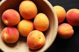 aprikoser i en träskål foto