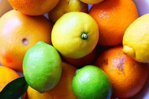 olika citrusfrukter i en keramisk skål foto