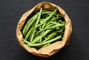 gröna bönor i en brun papperspåse