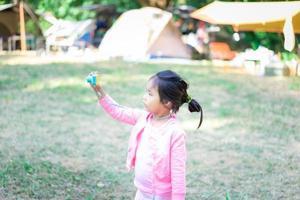 porträtt av söt liten asiatisk tjej som har kul med en leksakskamera foto