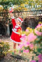 liten asiatisk tjej i röd jultomtendräkt