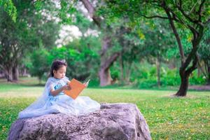 en liten söt asiatisk tjej som läser en bok