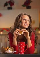 tankeväckande kvinna som har mellanmål i jul dekorerat kök foto