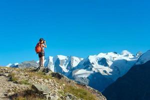 flicka fotograferar höga berg i Alperna foto