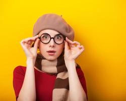rödhårig tjej i glasögon och halsduk på gul bakgrund.