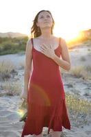 kvinna i röd klänning på stranden med handen över hennes hjärta