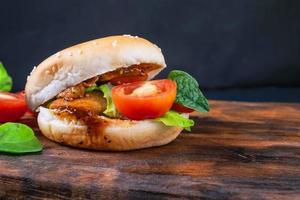färsk välsmakande hamburgare på träbakgrund foto