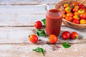 färsk tomatjuice med tomater i en korg foto