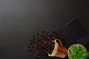 kaffebönor och smartphone på skrivbordet foto