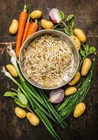 groddar i durkslag med färska ekologiska grönsaker för hälsosam matlagning