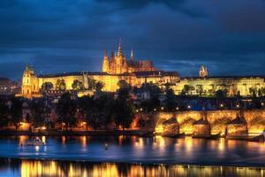 Prag panorama med charles bridge och Prague slott på natten