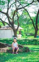 glad liten flickasammanträde på trädrot i parken foto