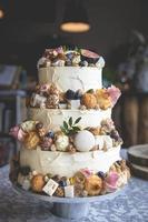 dekorativ bröllopstårta med frukt, kex, makron och blommor foto