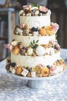 traditionell bröllopstårta dekorerad med frukt, kex, makron och blommor foto