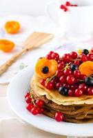 pannkakor med bär och frukt: aprikos, röd, svarta vinbär foto