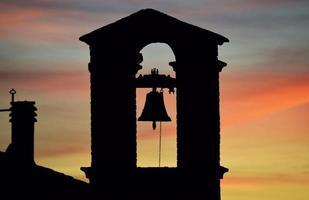 silhuett av kyrkliga klockan under solnedgången