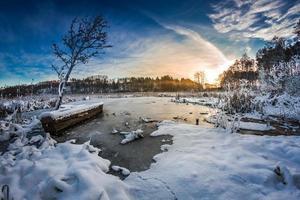 första snön på vintern vid sjön vid soluppgången