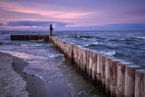solnedgång sprutande på vågbrytaren foto