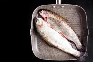 rå fisk i grillpanna foto