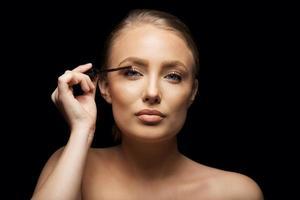 attraktiv kvinna som sätter mascara på ögonfransarna foto