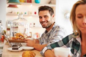 ung man med bärbar dator på ett kafé foto