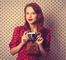 porträtt av rödhårig tjej med retro kamera