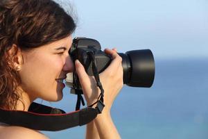 attraktiv kvinna som tar ett fotografi med sin kamera