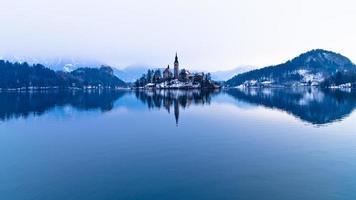 perfekt symetri av en sjö och kyrka på en liten ö foto