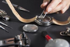 urmakare byter ut ett batteri foto
