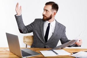 affärsman lyfter upp handen sittande vid skrivbordet