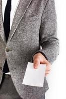 mannen i grå kostym håller tomt vitt kort