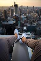 person som sitter ovanpå en stadsbyggnad med utsträckta ben