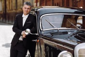 stilig brudgum i svart smoking poserar före en svart retro bil