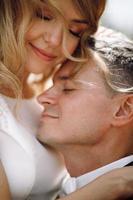 bruden och brudgummen omfamnar i solskenet foto
