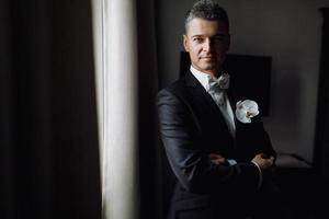 stilig brudgum i svart smoking står i ett mörkt hotellrum