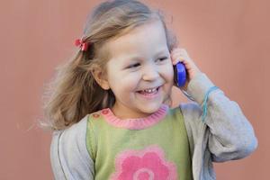 tjej som har kul under sin dialog med mobiltelefonen