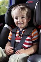 ungt barn i en bilstol i en röd skjorta foto