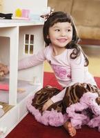 liten flicka med dockhus foto