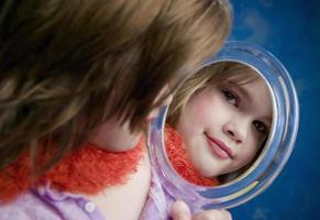 liten flicka som ser en spegel
