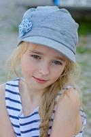 porträtt av liten flicka i denim mössa utomhus