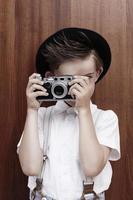 ung pojke som tar fotografi med gammal kamera foto