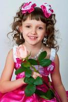 flickan i en vacker klänning med ros foto